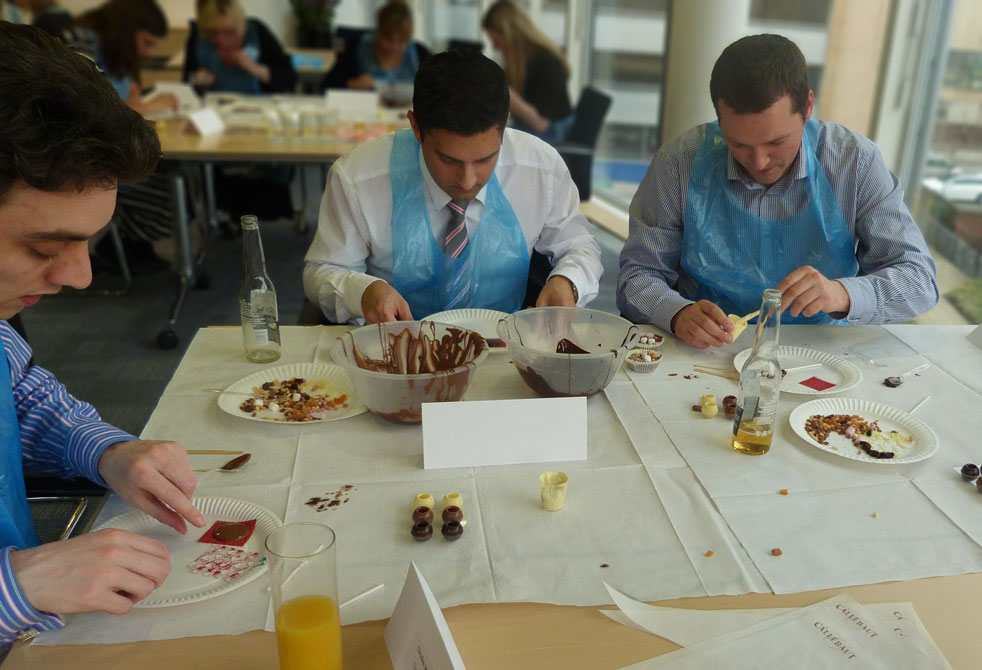 Three men making chocolate at a chocolate masterclass
