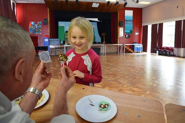 Young girl being shown her chocolate lollipop
