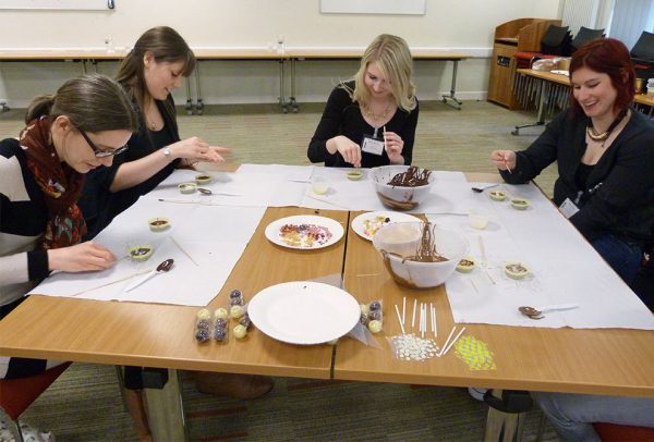 Four ladies making chocolates at a chocolate masterclass - Huddersfield University Staff